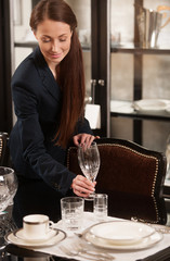 Woman serving table. Beautiful young woman in formalwear serving