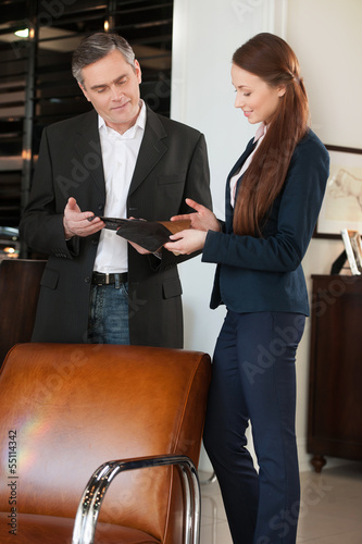 Man in furniture store. Confident mature man talking with sales