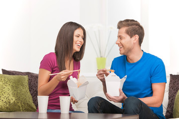 Eating Asian food. Beautiful couple eating Asian food from food