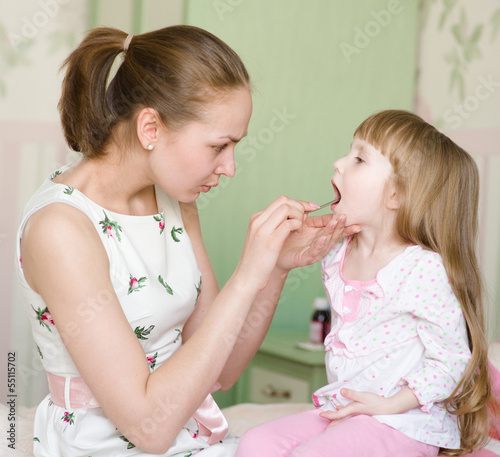 mother examining little girl's throat