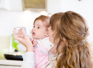 Mother feeding baby with feeding bottle in kitchen