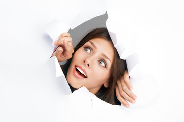 Young woman breakign through a paper sheet