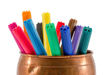 copper box full of colorful felt-tip pens on white