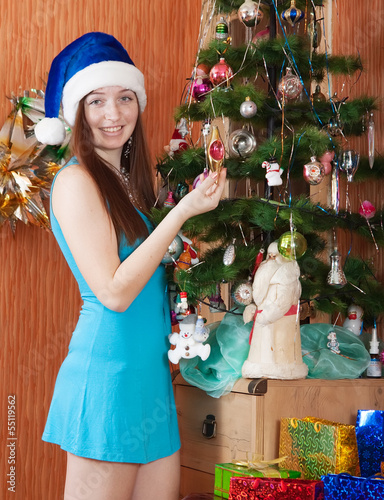 Girl near decoration spruce