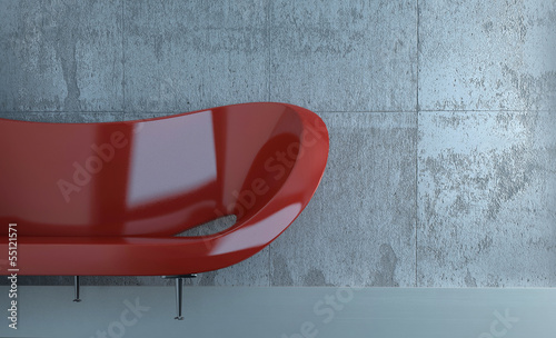 Red couch against concrete wall