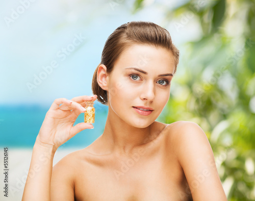 beautiful woman showing bottle with golden dust