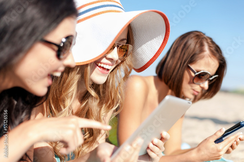 girls with tablet pc on the beach