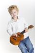 Toddler is playing on ukulele