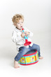 Toddler is playing with toy musical instruments