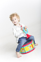 Young boy is playing with bright toy musical instruments