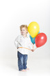 Happy cute boy with bright balloons