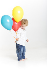Toddler with bright balloons isolated on white