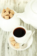 Cup of coffee, teapot and sugar-bowl on color wooden background