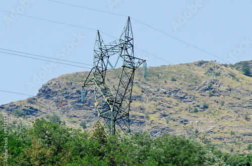 electricity pylon with green forest