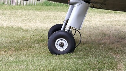 Stationary Small Plane Wheels And Blowing Grass