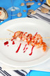 Grilled shrimp with sauce on plate on wooden table close-up