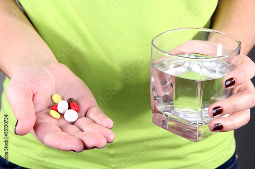 Many pills and glass water in hand