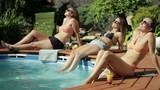 Three female friends sunbathing by the pool