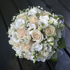 Wedding bouquet of yellow and cream roses lying on wooden floor