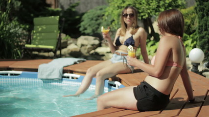 Two female friends sunbathing and chatting by the pool