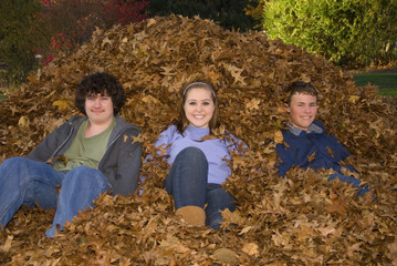 Raking Leaves Three Teens Sitting in Leaf Pile