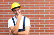 Thinking young worker in front of a brick wall