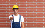 Pointing young worker in front of a brick wall