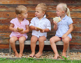 Funny kids with snack sitting on a wooden bench.