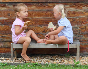 Little girls with snack sitting on a wooden bench.