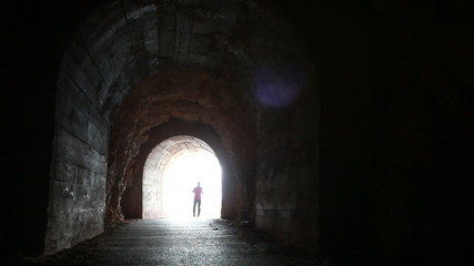 Man runs through the dark concrete tunnel