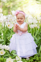Little girl in an elegant dress to stand near blossoming tulips