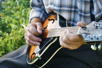Senior man playing mandolin