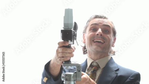 man in lounge suit with old movie camera over white background