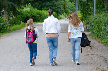 Girls with mother on the way back home from school