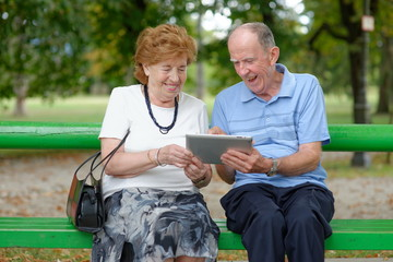 Two senior people sitting with a tablet PC in a nature park