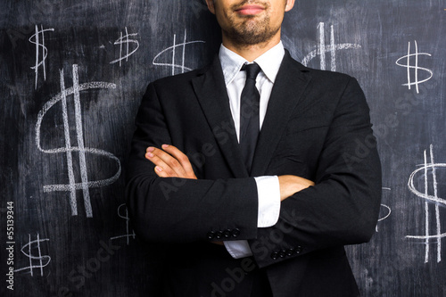 Successful businessman posing in front of dollar signs