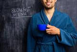 Man in robe next to breakfast menu on blackboard