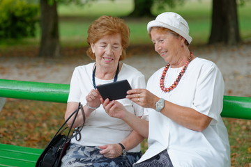 Two senior ladies reading news on tablet in the park