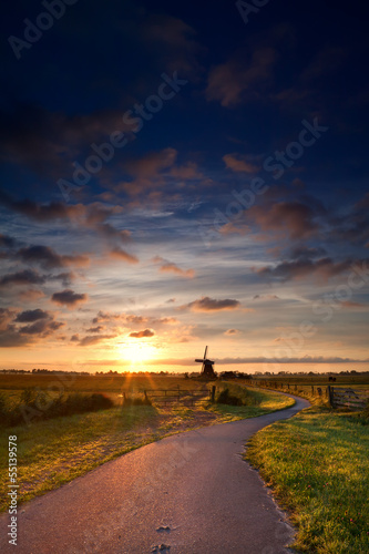 warm summer sunrise and windmill