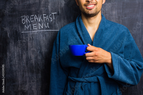 Man in robe next to breakfast menu on blackboard