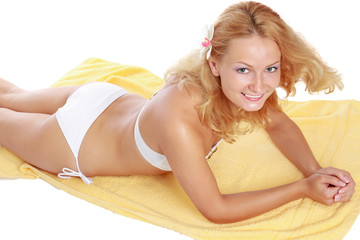 A  woman in a white swimsuit is lying on a yellow towel