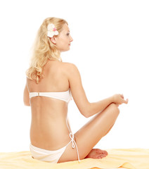 A young woman in a swimsuit meditating