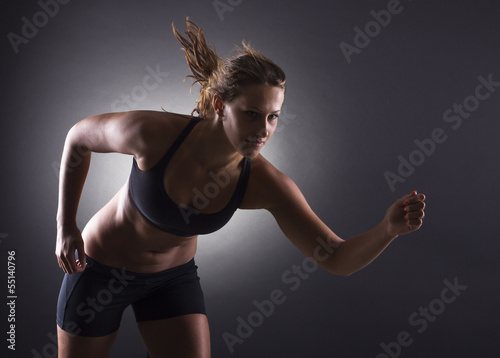 Woman running on a dark background.