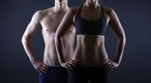 Starker Mann und eine Frau, posiert auf einem schwarzen Hintergrund
