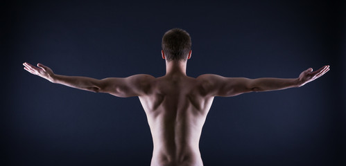 athlete stands with his back against a black background