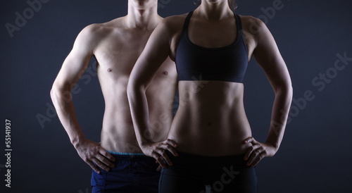Strong man and a woman posing on a black background - 55141937