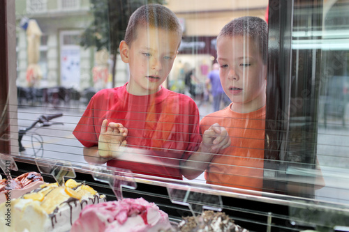 Two young boys looking ice cream in pastry shop