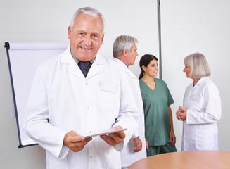 Arzt mit Tablet PC und Team