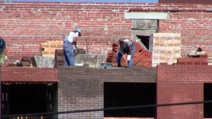 Works at the construction site. Bricklaying