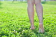Walking barefoot on green grass women legs. Copyspace